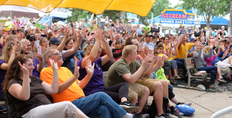Crowd raising their hands and smiling at Baldwin Family Park